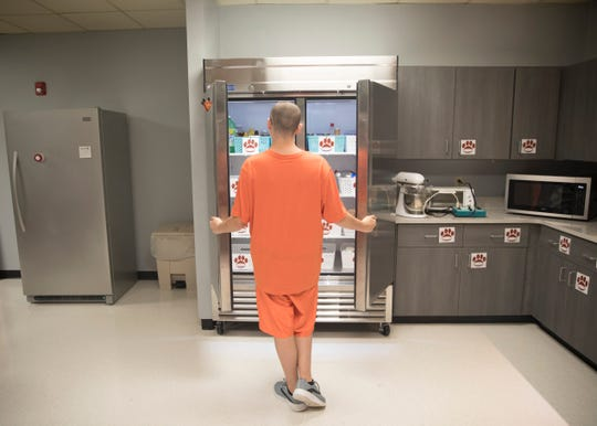 """John """"Miko"""" Hicks looks inside the refrigerator, acquired with help from the No Kid Hungry organization, used in the Pioneer School's daily living home training room. Many of the other appliances used and kitchen cabinetry were acquired thanks to a grant from Lowe's. """"I like the oven and the fridge the most,""""  said Hicks. """"People need to learn how to bake and do laundry."""""""