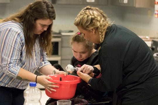Lydia Reichert, left, and Kelli McDonald, right, help Destiny Cantrill scoop ice cream to make punch to have with cookies being baked inside Pioneer School's daily living home training room.
