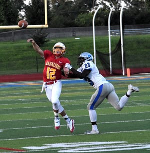 Purcell Marian Quarterback Zach Hoover (12) unloads a pass to the sidelines while in the grip of Summit Country Day's Alonzo Motley (23), August 22, 2018.