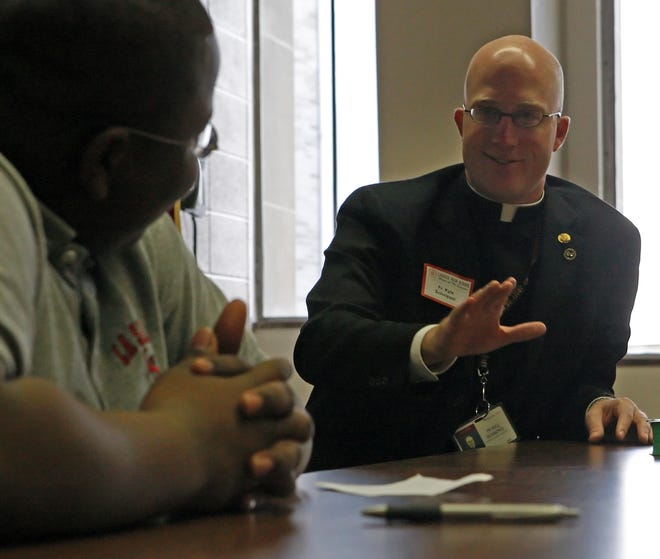 PRIESTRECRUITER. METRO. November 10, 2008. Father Kyle Schnippel, who runs the Archdiocese's Vocations Program, talks to a group of students at Lasalle High School for a career day, including Mailk Shabazz (left), the morning of November 10, 2008. The Enquirer/Amie Dworecki