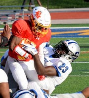 Torrance Johnson of Purcell Marian is dropped by Alonzo Motley (23) of Summit Country Day afte ra short gain, August 22, 2018.