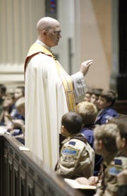 The Rev. Kyle Schnippel presides over a ceremony Sunday in which more than 100 Roman Catholic Cub Scouts, Webelos, Boy Scouts and Venturers received religious emblems from the Archdiocese of Cincinnati Catholic Committee on Scouting at the Cathedral of St. Peter in Chains.  The Enquirer/Amanda Davidson SCOUTCEREMONY: Sunday, January 22, 2012: LOCAL/ METRO. Fr. Kyle Schnippel presides over a ceremony in which more than 100 Catholic Cub Scouts, Webelos, Boy Scouts and Venturers received religious emblems from the Archdiocese of Cincinnati Catholic Committee on Scouting at the Cathedral of St. Peter in Chains on Sunday.  The Enquirer/ Amanda Davidson