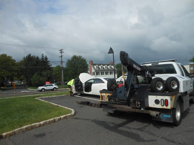 The tow truck employee working on the woman's car in the Kings parking lot in Bedminster before taking it to the mechanic.