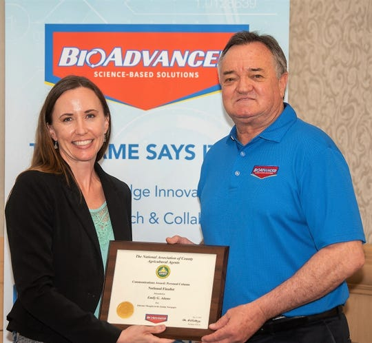 Emily Buxton Adams receives an award from Lance Walheim of BioAdvanced, sponsor of communications awards by the National Association of County Agriculture Agents. The Coshocton County office of Ohio State University Extension was recently honored for its women in agriculture website and a personal column written by Adams for the Coshocton Tribune.