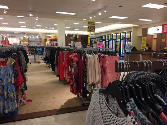 Signs tout 70 percent off sales, plus an additional 30 percent, on clothing at the Younkers' store at Merle Hay Mall last week. The store closes for good on Wednesday.