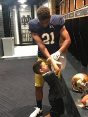 Four-star RB Gavin Williams lets his little brother, Brayden, help him put on gloves during a late-June unofficial visit to Notre Dame.