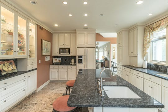 The remodeled kitchen has white cabinets, granite counters, a walk-in pantry with a second refrigerator, and built-in appliances, including a wine cooler. There is a nearby laundry room with sink and cabinets.