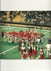 Members of the 1993 City High football team celebrate after winning the state championship game at the UNI-Dome in Cedar Falls.