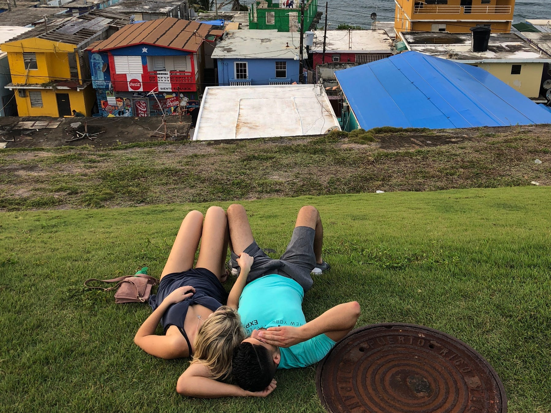 Ten months after Hurricane Maria hit Puerto Rico blue tarps can still be seen on rooftops in old San Juan as a couple lays on the grass in the evening facing the Atlantic Ocean.