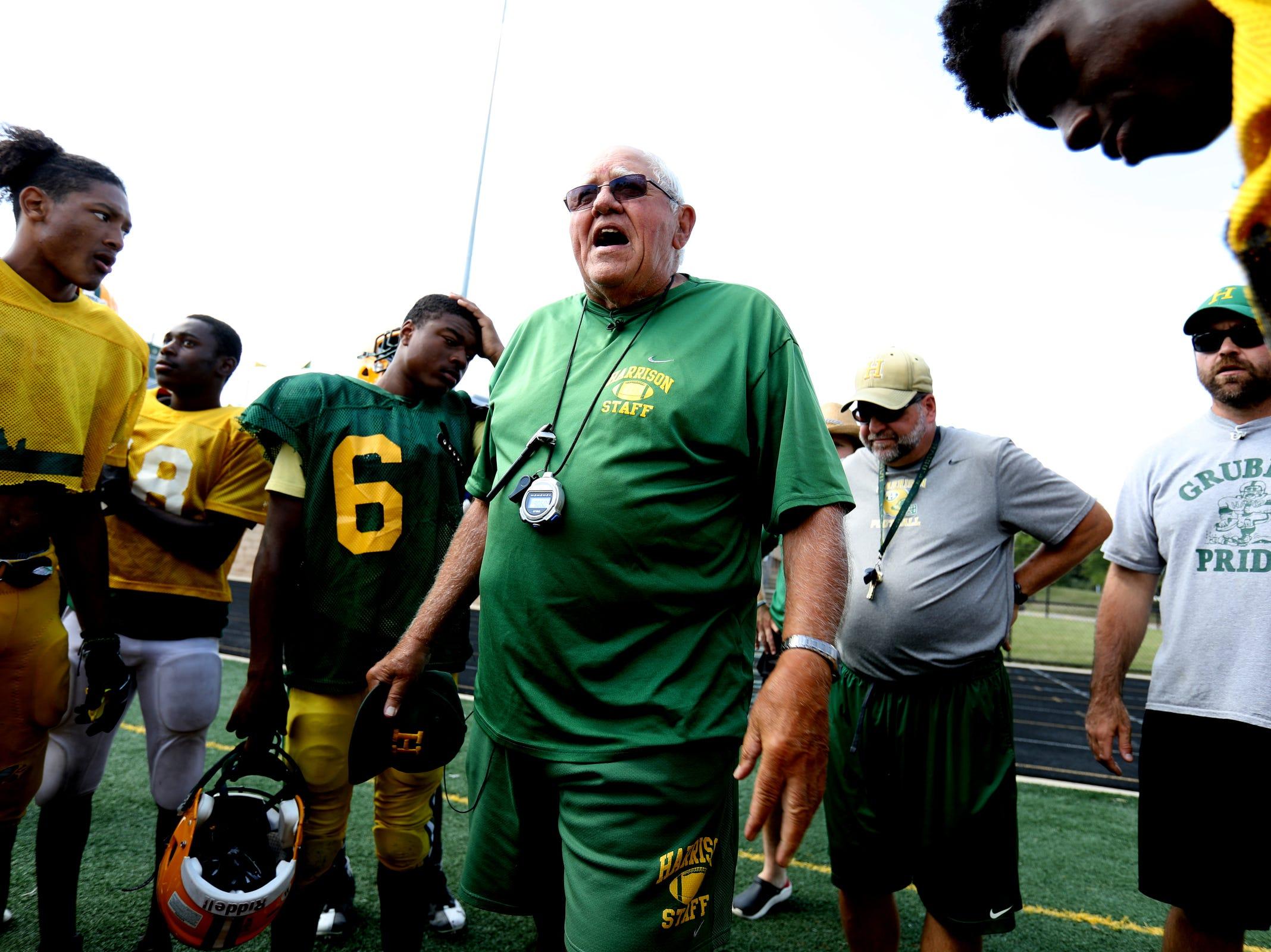 Farmington Hills Harrison High School football coach John Herrington talks with players during a huddle after practice at the school in Farmington Hills on Thursday, Aug. 23, 2018.