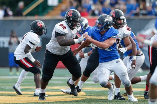 Oak Park offensive line Justin Rogers (52) faces Utica Eisenhower Justin Trpcevski (52) during the second half of a Prep Kickoff Classic game at Wayne State University's Tom Adams Field in Detroit, Thursday, August 23, 2018.