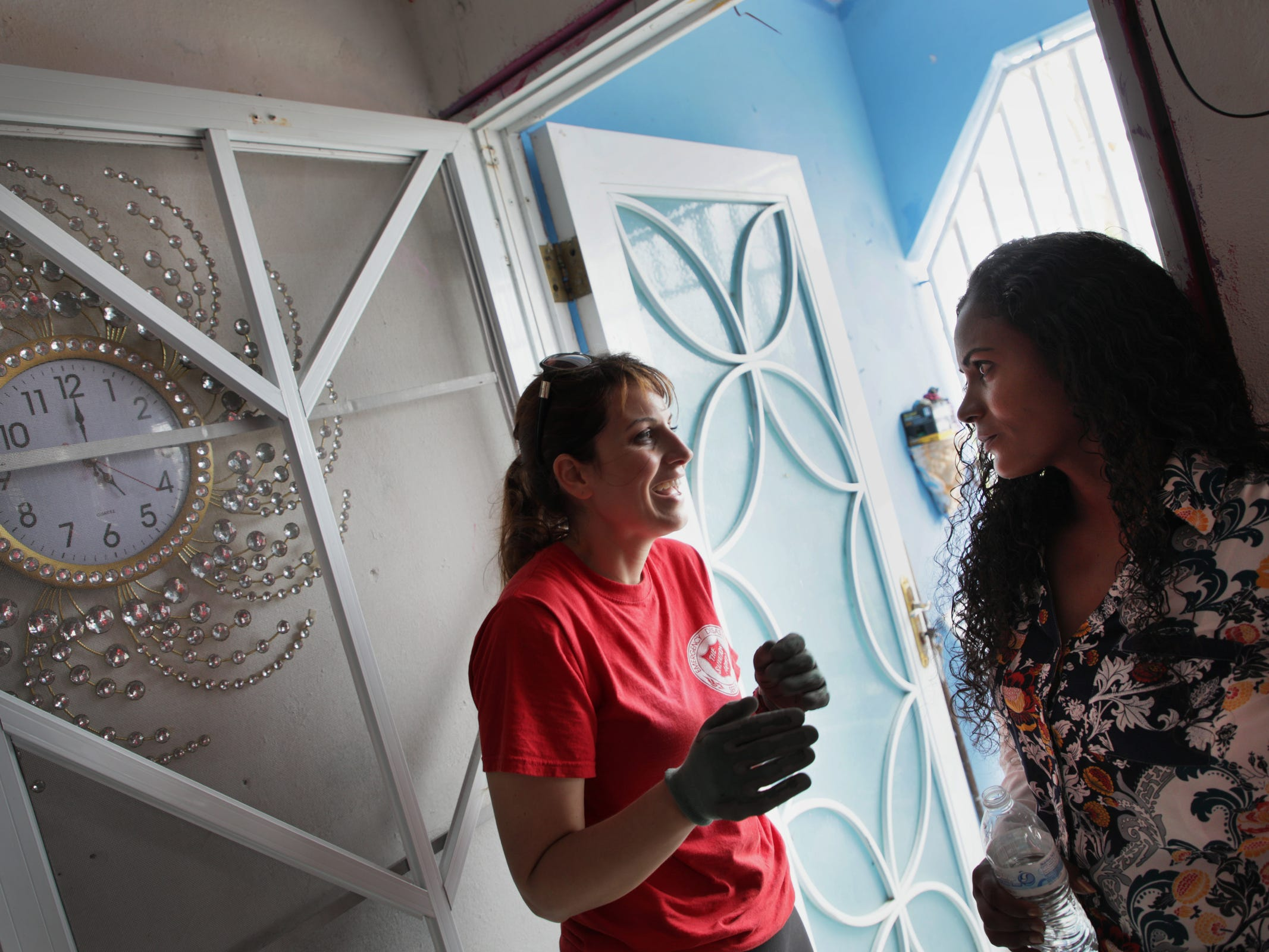 Nicky Roy, Salvation Army coordinator for long-term recovery, left and Taina Castro Cruz, 38, a former receptionist who assists the Salvation Army helping others talk during a home visit in Yabucoa, Puerto Rico.
