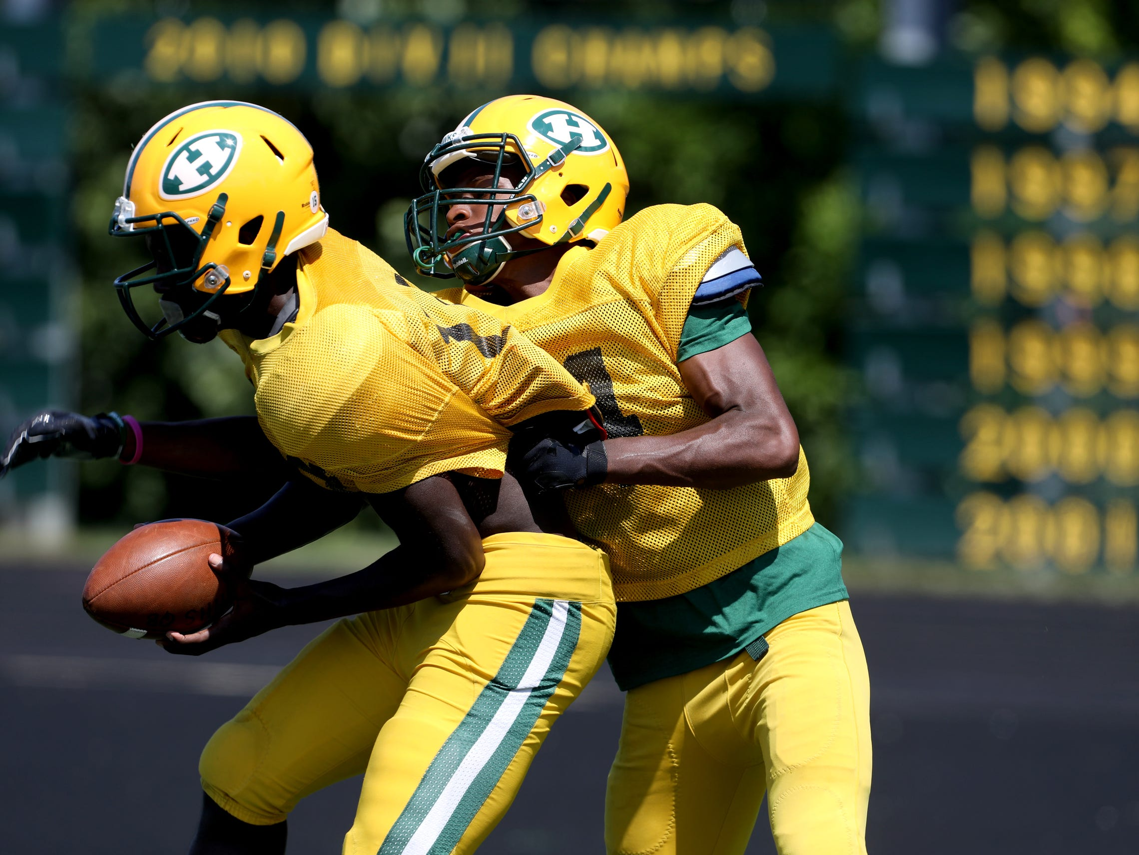 Malcolm King steps in front of Rod Heard during for the catch during end zone drills during Farmington Hills Harrison High School football practice at the school in Farmington Hills on Thursday, Aug. 23, 2018.