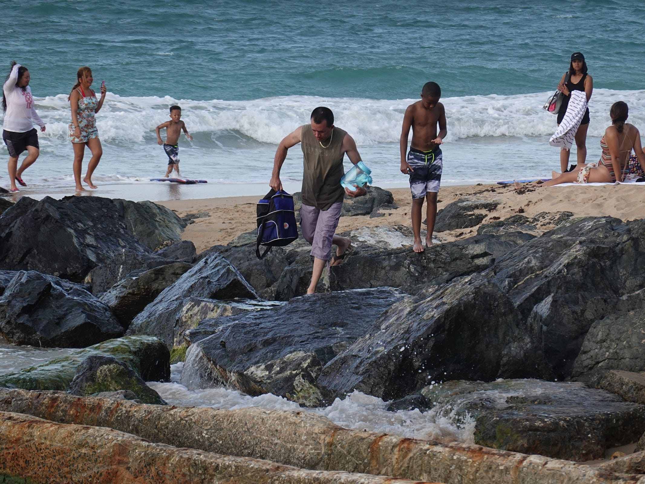 Ten months after hurricane Maria hit Puerto Rico people walk around the beach on the Atlantic Ocean in San Juan.