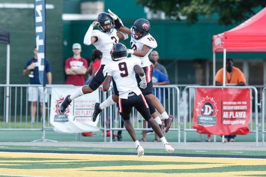 Oak Park defensive back Enzo Jennings (3) celebrates a touchdown against Utica Eisenhower with Jalen Fielder (10) and Corion Montgomery (9) during the first half of a Prep Kickoff Classic game at Wayne State University's Tom Adams Field in Detroit, Thursday, August 23, 2018.