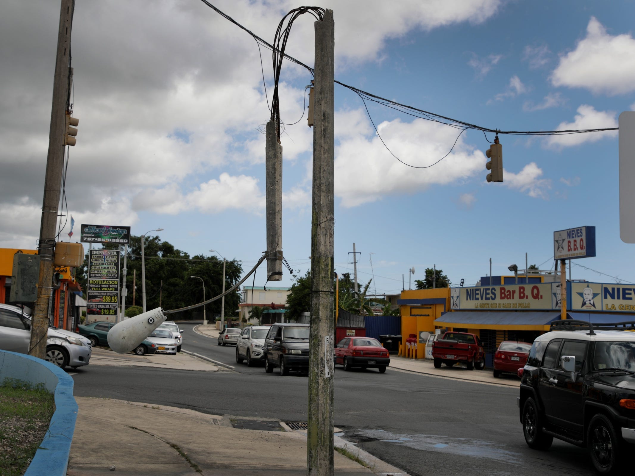 Some traffic lights still are not working and a street light stands bent in half ten months after Hurricane Maria hit Puerto Rico in Bayamon.