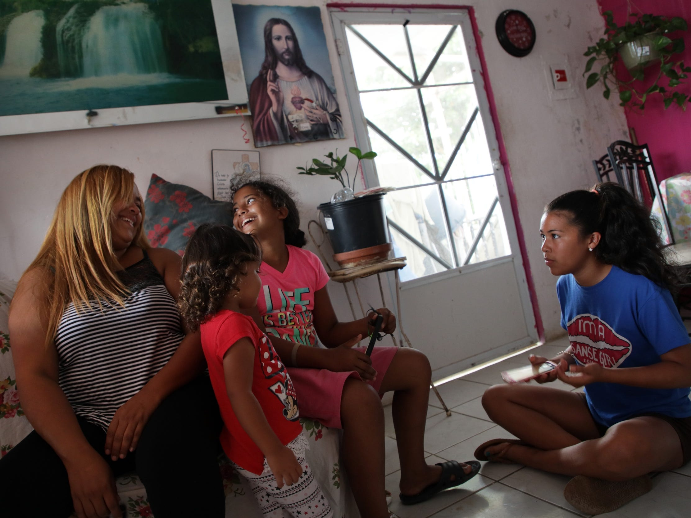 (l to r) Liz Velazquez, shares a laugh with Tayra Beltan, 2 and Nayeli Aponte, 12 as Neysha Gonzalez, 13, looks on in the living room they share with 5 other family members in Yabucoa, Puerto Rico.