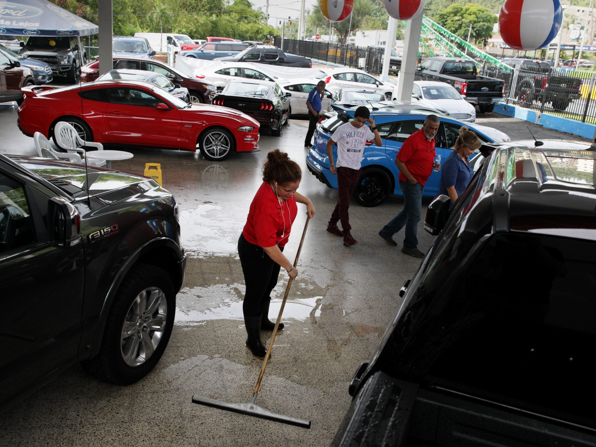 Sol Lorenzana dries the showroom floor at Caguas Expressway Motors after a morning rain as the dealership still works to fix their facilities ten months after Hurricane Maria hit the island in Caguas, Puerto Rico.