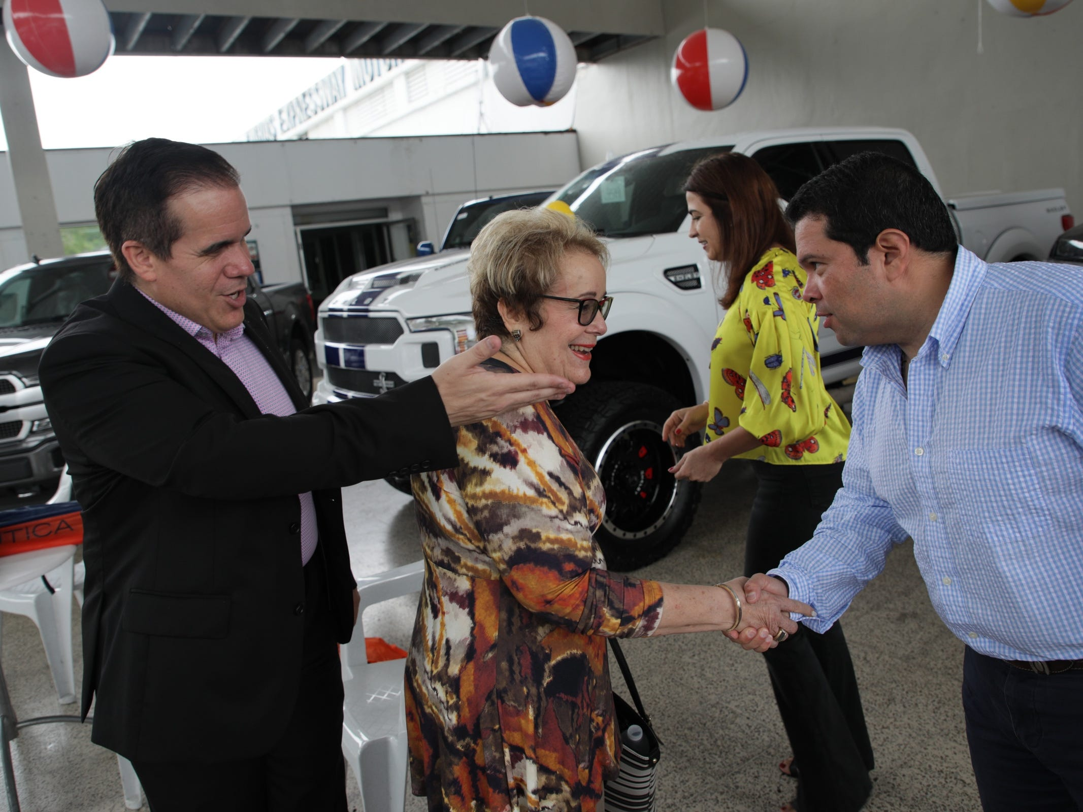 (l to r) Julio Ortiz, vice president of Caguas Expressway Motors, from left introduces his mother Elva Mendez, president of Caguas Expressway Motors to Joe Avila of the Ford Fund at their Ford dealership in Caguas, Puerto Rico.