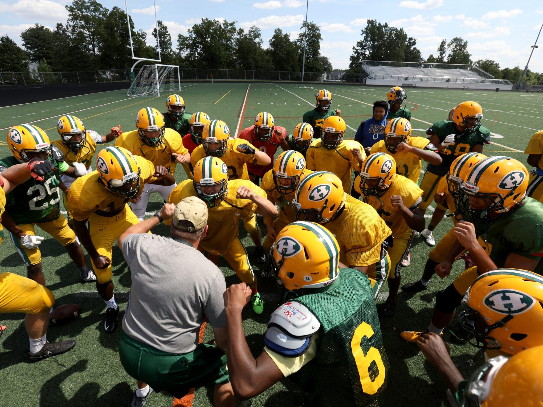 Farmington Hills Harrison High School defensive coordinator Dave Thorne huddles up his team after practice at the school in Farmington Hills, Michigan on Thursday, Aug. 23, 2018.