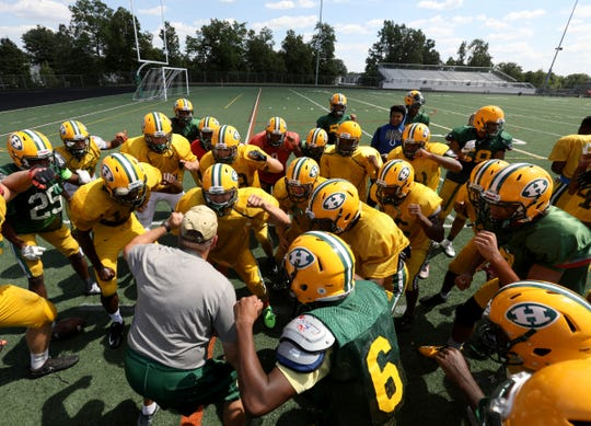 Farmington Hills Harrison High School defensive coordinator Dave Thorne huddles up his team after practice at the school in Farmington Hills, Michigan on Thursday, Aug. 23, 2018.