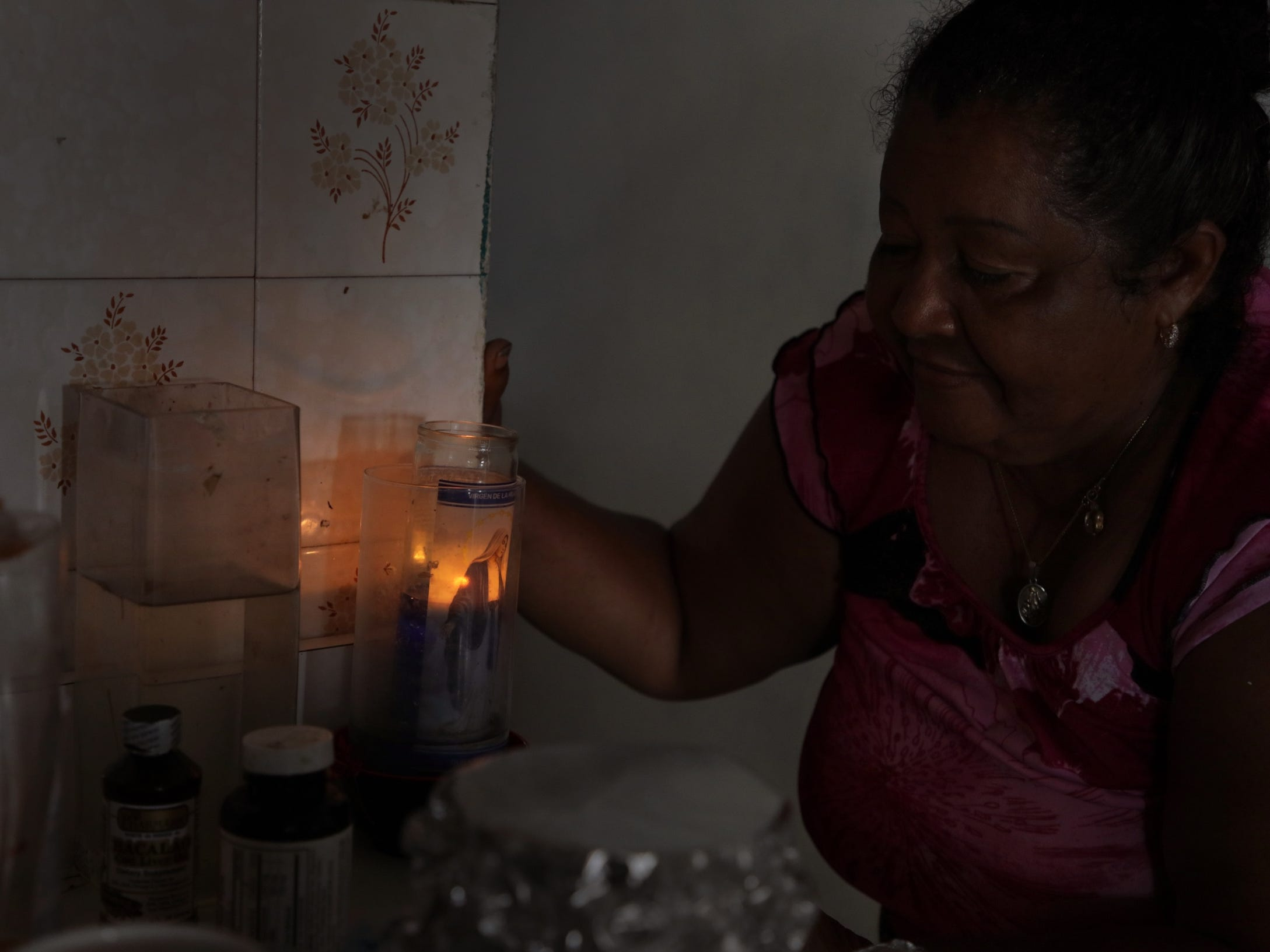 Crucita Velazquez, 63 tends to the candle she lights daily asking for protection from the virgin Mary in her kitchen in Yabucoa, Puerto Rico.