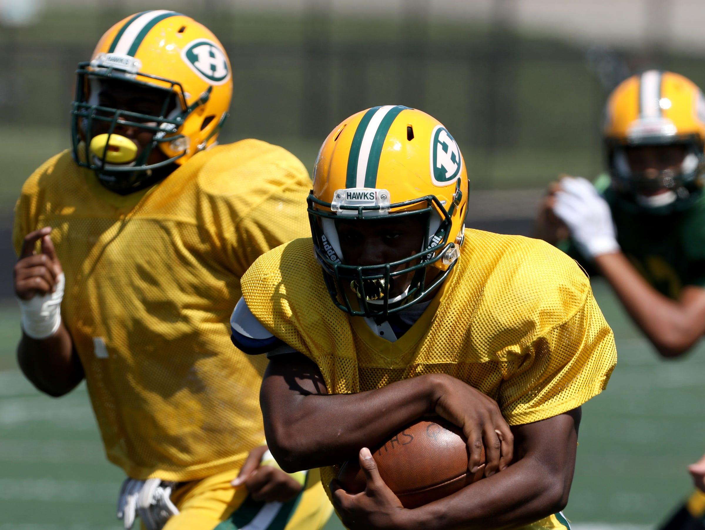 Vincent Rawls takes the handoff and runs down the field during Farmington Hills Harrison High School football practice at the school in Farmington Hills on Thursday, Aug. 23, 2018.