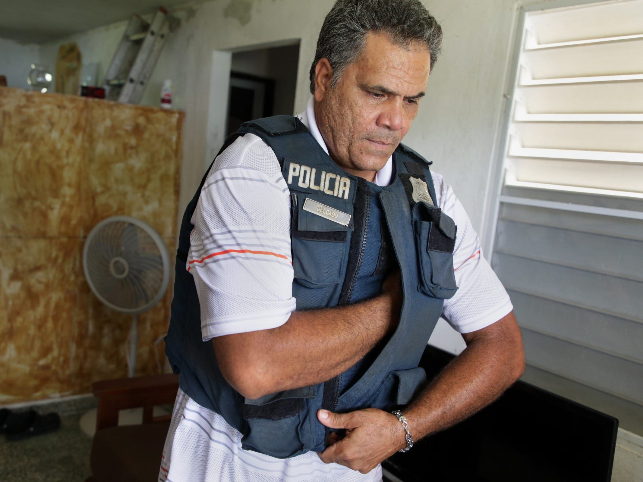 Eleobadis Delgado, 49 tries on his body armor at his home in Maunabo, Puerto Rico. The body armor protects his 6-foot-2-inch frame. But the 19-year policeÊveteran says nothing can protect him from the nightmares of failed rescues and destroyed homes he has seen since Hurricane Maria last year devastated his island