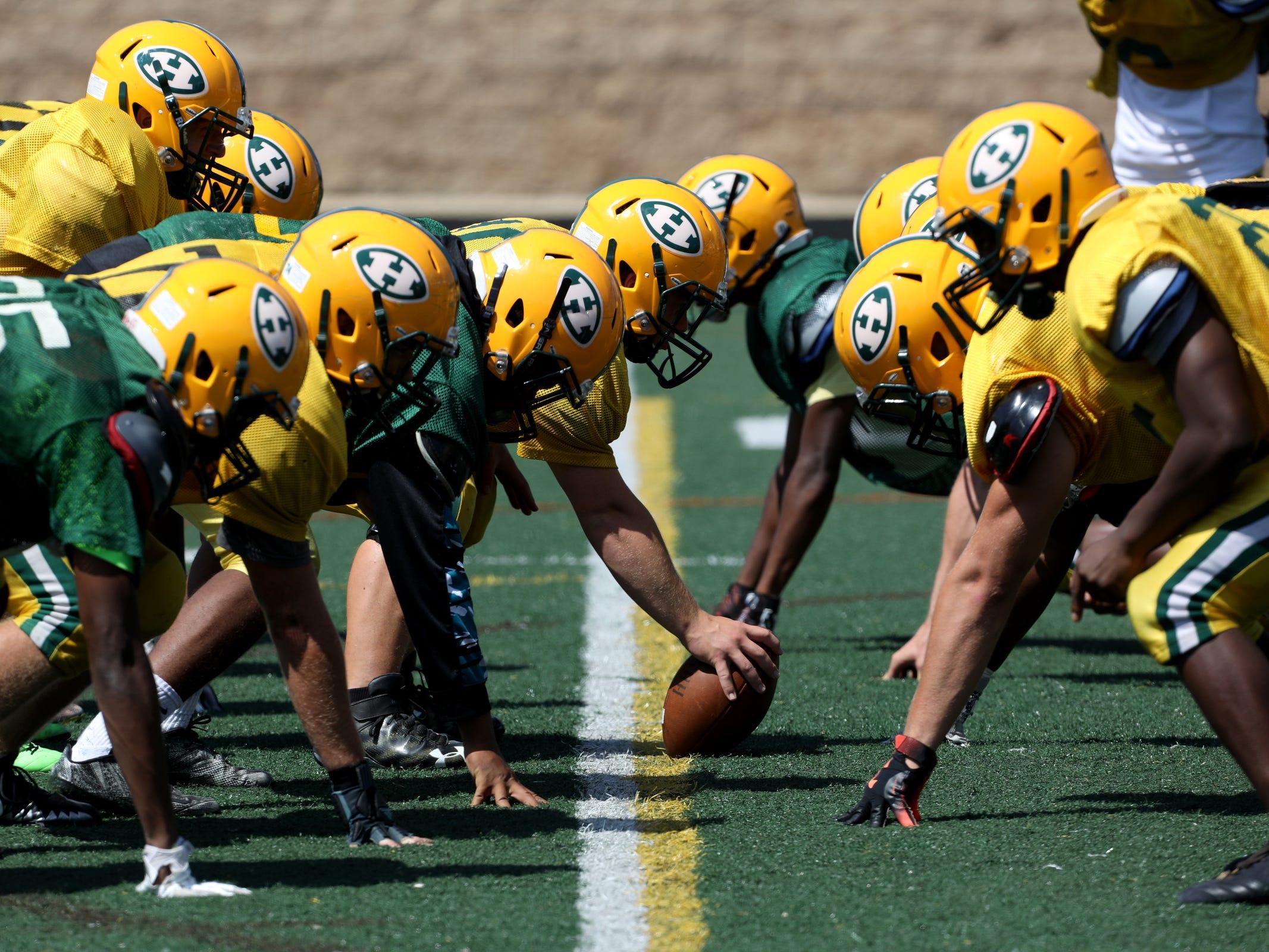 The Farmington Hills Harrison High School football team practice at the five yard line during end zone drills during Farmington Hills Harrison High School football practice at the school in Farmington Hills on Thursday, Aug. 23, 2018.