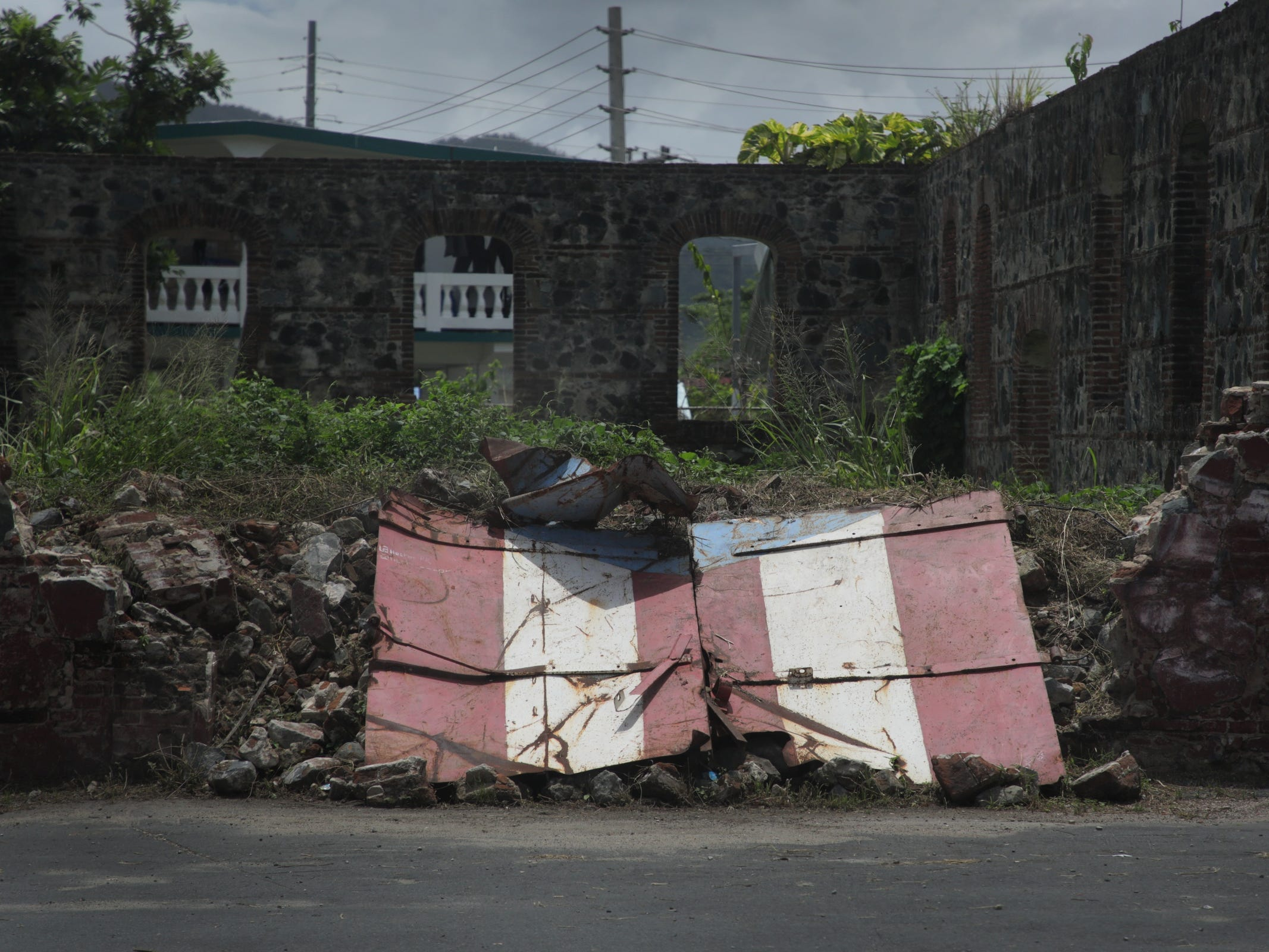 A gate with the Puerto Rican flag lays crushed by a collapsed wall on the side of the road in Yabucao, Puerto Rico.