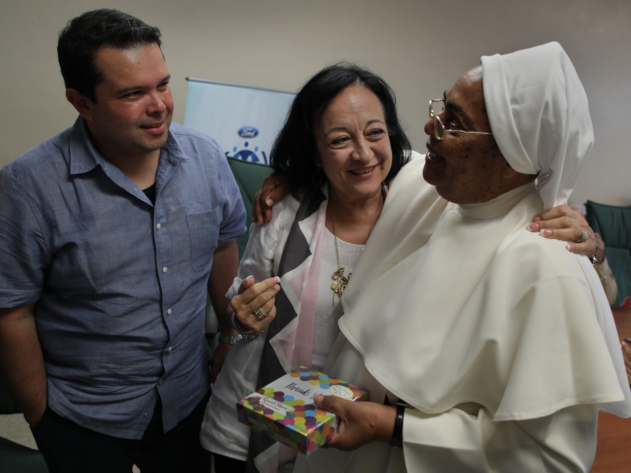 (l to r) Joe Avila and Gloria Rodriguez of the Ford Fund share a moment together with sister Virgenmina Morell, 75, at Centros Sor Isolina Ferré in Ponce in Puerto Rico.