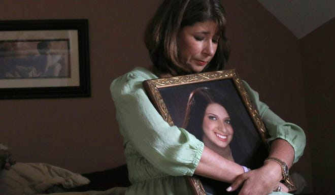 Alicia Stillman holds a photo of her daughter Emily Stillman, who died of bacterial meningitis in 2013.