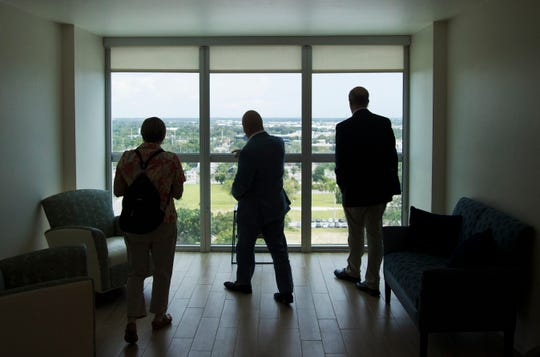Rob Harris, center, the owner and developer of Campo Felice, leads a tour on Wednesday of the independent senior living community in downtown Fort Myers.