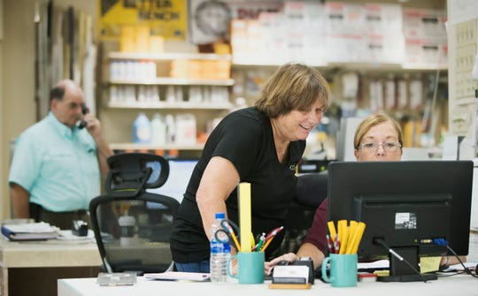 Helene Glocer, center, owner of PCC Tile, and Cherly Cinq-Mars, help customers on Thursday at the store in south Fort Myers. The store suffered severe damage in the Island Park flooding last August.
