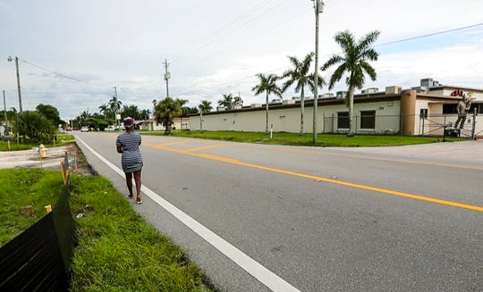 Tahara Wilson, 21, walks on the side of Hanson Street to get home after visiting the gas station at the corner of Cleveland Avenue and Hanson. She said the road is very dangerous and sidewalks are needed.