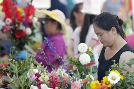 Ia Lee arranges flowers at her booth at the Saturday Farmers Market in downtown Green Bay.