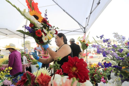 Ia Lee puts together a bouquet at her booth at the Saturday Farmers Market. She grows her flowers on a 3-acre field in Ledgeview.