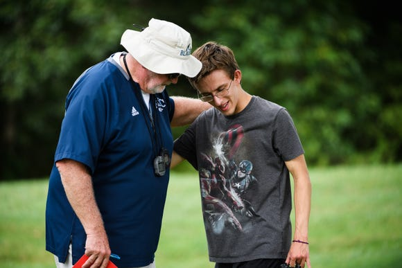 Louden Craig, 17, speaks with his cross country coach David Smith during practice at Greer Middle College Charter High School on Wednesday, Aug. 22, 2018.