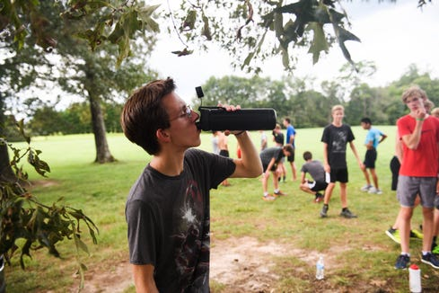 Louden Craig, 17, takes a drink from his water bottle after running with his cross country teammates at Greer Middle College Charter High School on Wednesday, Aug. 22, 2018.