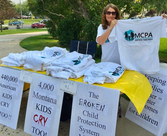 Georgia Miller, secretary of Montana Child Protection Alliance, holds up a T-shirt for sale at Thursday's rally.