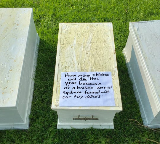 Some small caskets dotted the Capitol lawn, depicting the children who died in the care of the state.