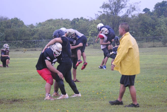 Simon Sanchez coach Jimmy Naholowaa works his players through drills in the rain at the school campus on Aug. 21