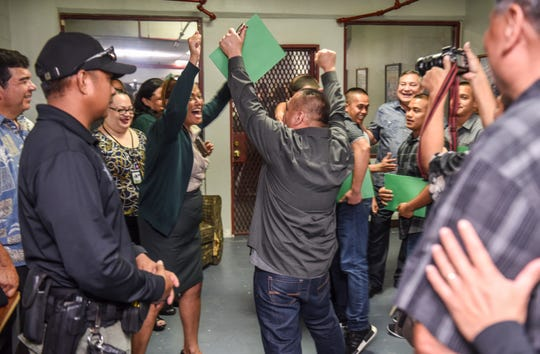 A graduate of the Department of Corrections' Residential Substance Abuse Treatment program celebrates with DOC personnel in this Aug. 23, 2018, file photo after then-Gov. Calvo signed commutation to parole documents. DOC will host a job fair for convicts part of the program to help them transition into the community.