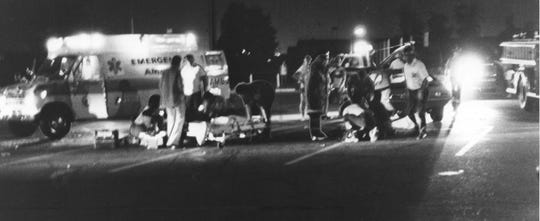 Emergency personnel attend to a victim of the Speedway bomber. The eighth bomb to hit Speedway in five days exploded Sept. 6, 1978 in the parking lot of Speedway High School shortly after a freshman football game. Three person were injured, one critically. Carl DeLong and his wife, Sandy were injured.