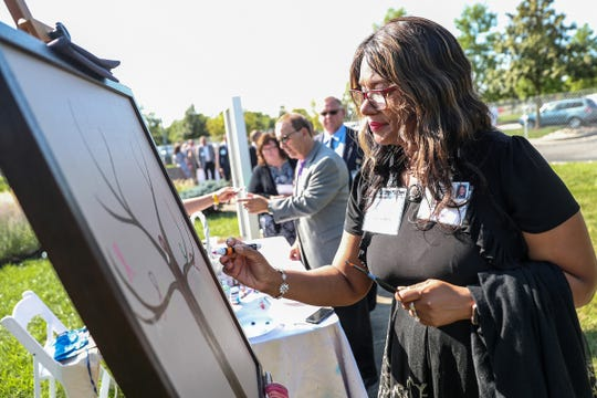 Tamarah Brownlee contributes to a piece of art that will hang in the $55 million Schwarz Cancer Center to be built on the Indiana University Health North Hospital campus in Carmel, Ind., during a groundbreaking ceremony, Thursday, Aug. 23, 2018.