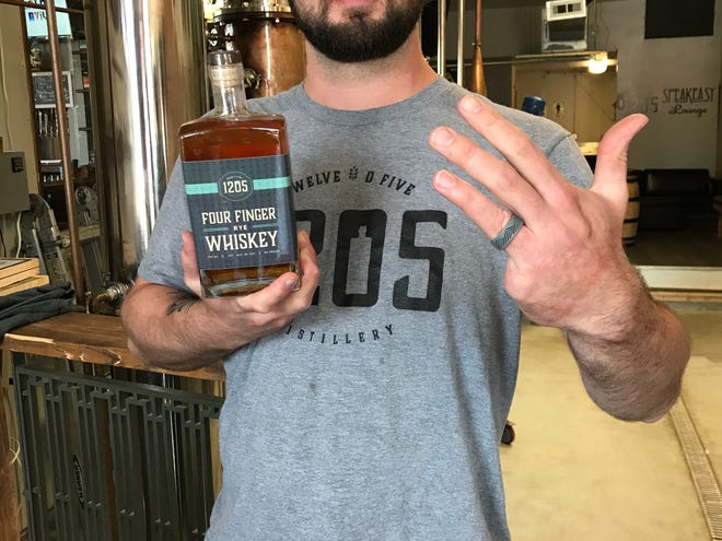 1205 Distillery co-owner Brad Colver, holding his Four Finger Rye Whiskey and showing off his pinky-less hand.