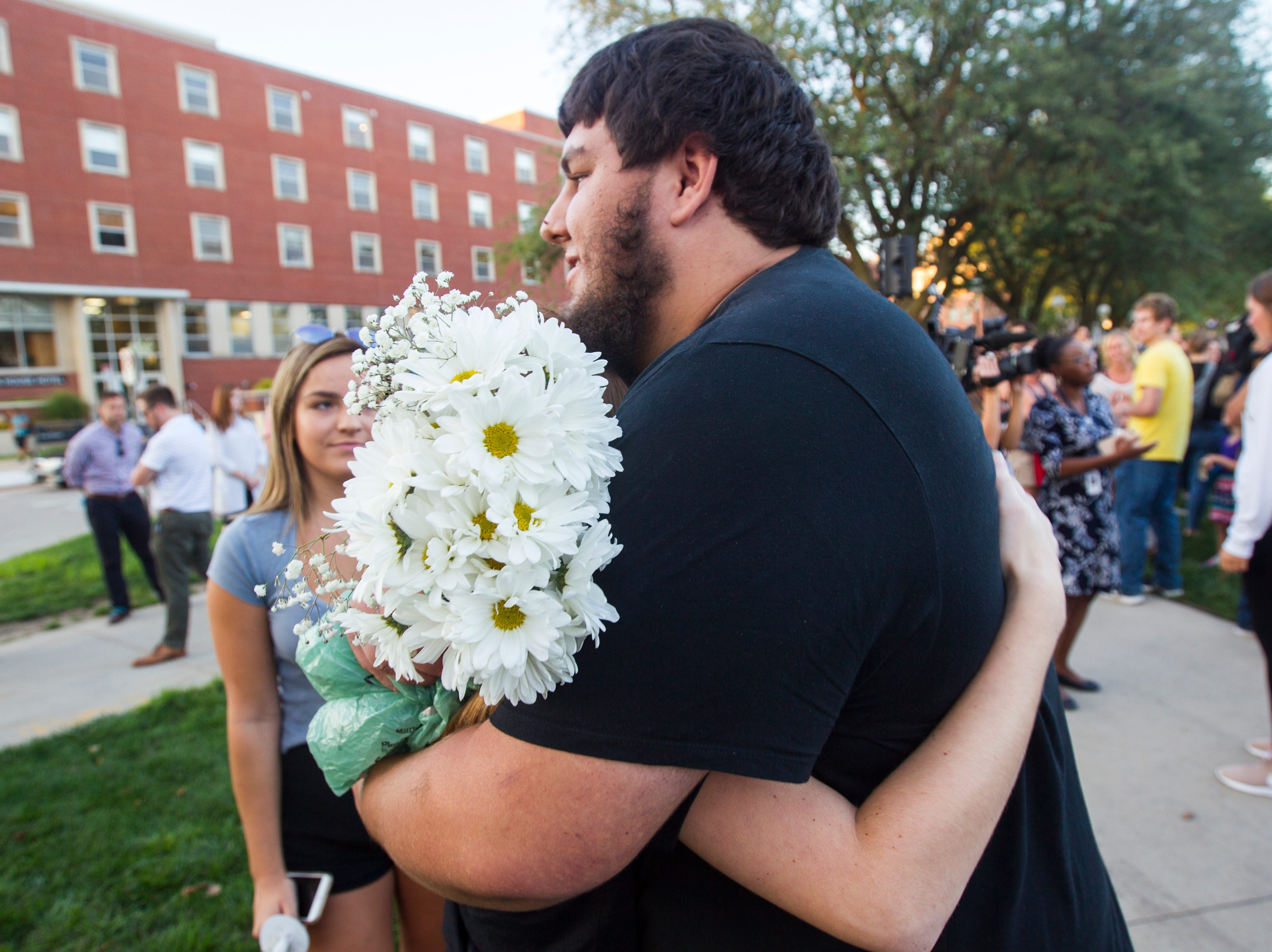 A supporter embraces Jake Tibbetts, the brother of Mollie Tibbetts, during a vigil for Mollie Tibbetts on Wednesday, Aug. 22, 2018, in Hubbard Park on the University of Iowa campus in Iowa City.
