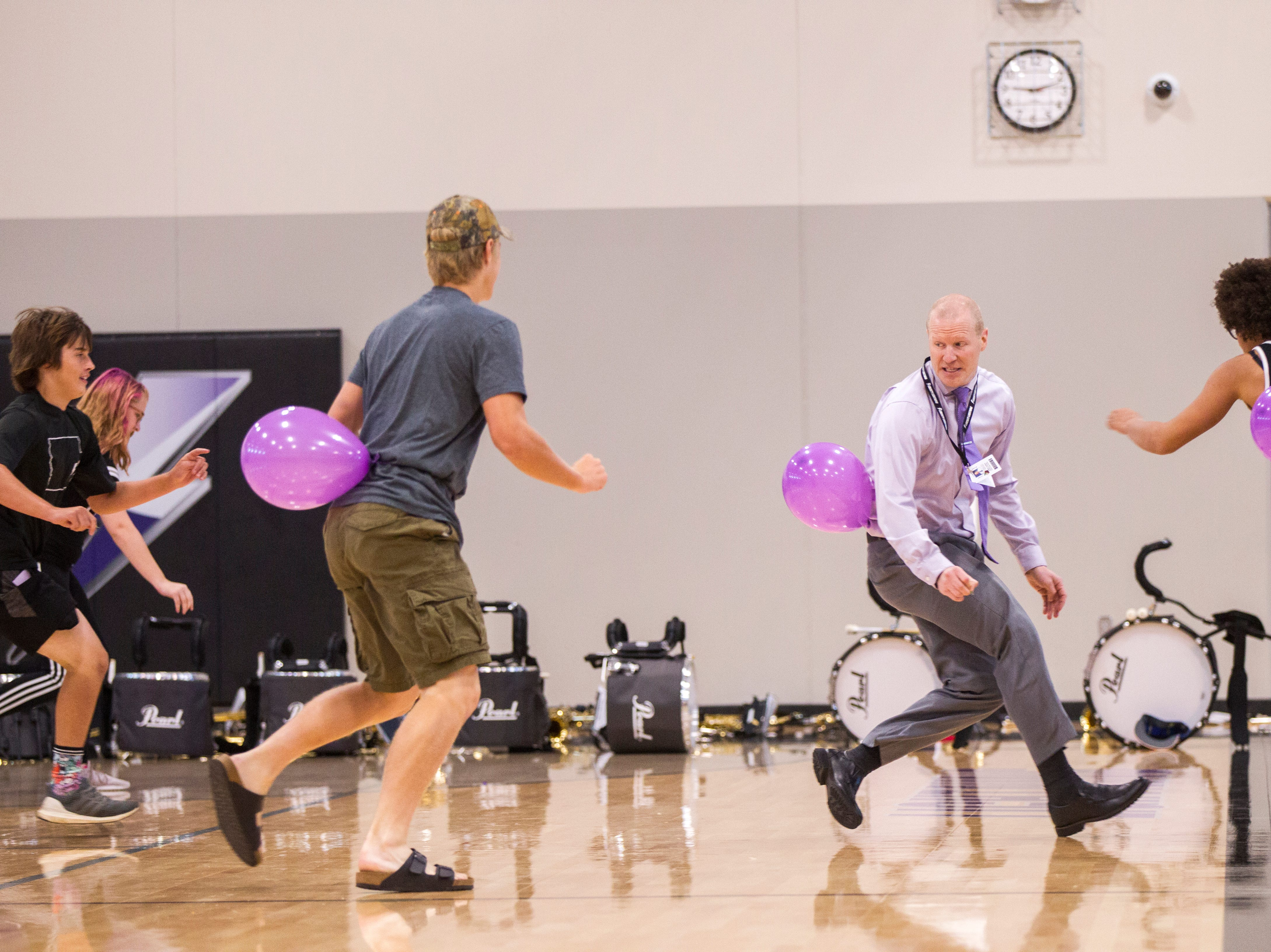 Justin Colbert, Liberty assistant principal, attempts to avoid getting his balloon popped by students while playing a game during a first day of school assembly on Thursday, Aug. 23, 2018, at Liberty High in North Liberty. Colbert played football at Drake from 2004-07.