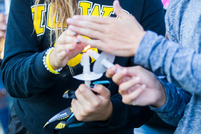 Students light each others candles during a vigil for Mollie Tibbetts on Wednesday, Aug. 22, 2018, in Hubbard Park on the University of Iowa campus in Iowa City.