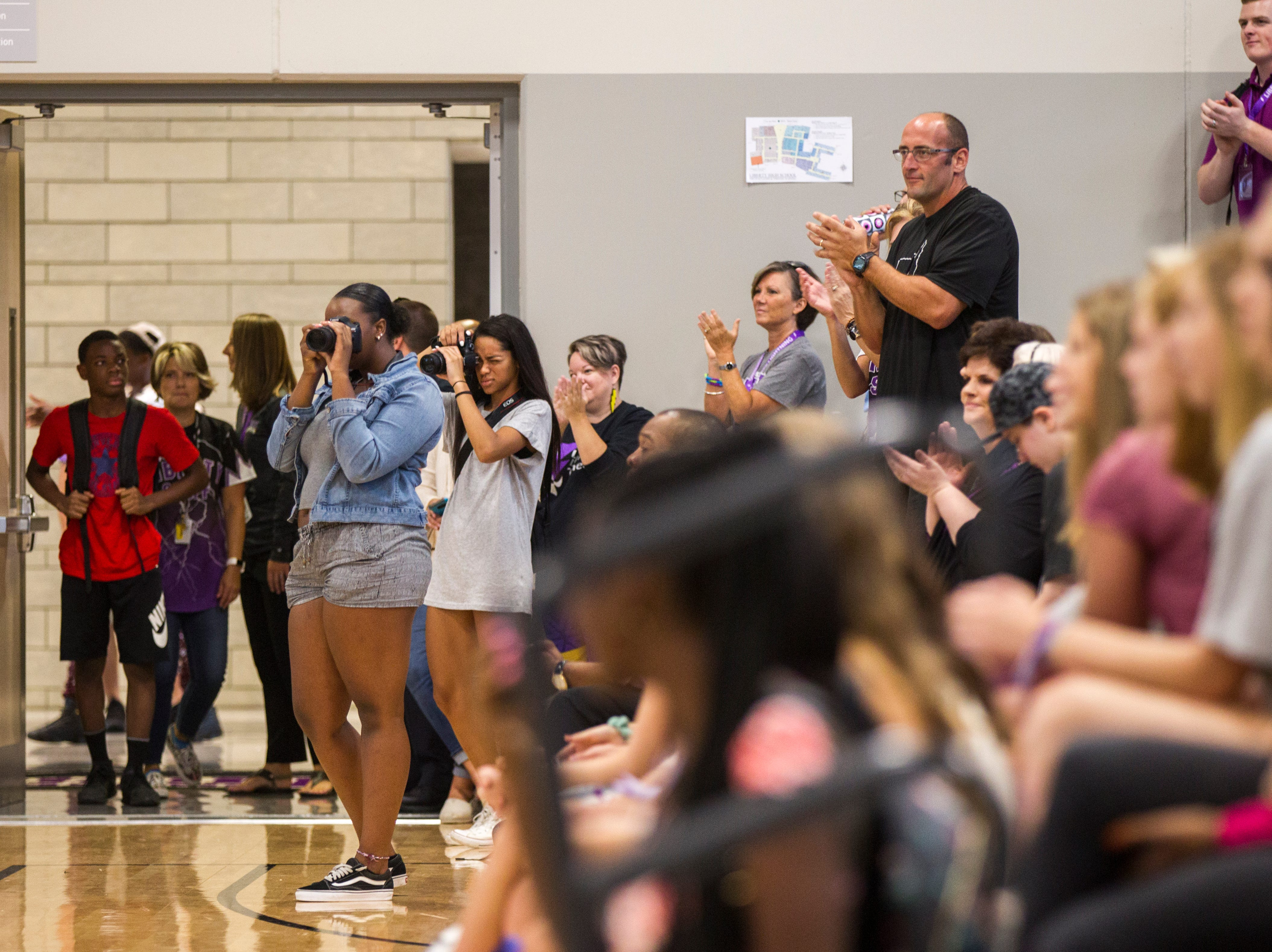 Jeff Gordon, Liberty football head coach and social studies teacher, (second from right) stands while the marching band plays a fight song during a first day of school assembly on Thursday, Aug. 23, 2018, at Liberty High in North Liberty.